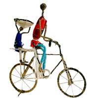 Model bike, cyclist with child, basket on head